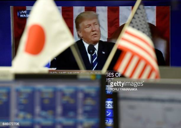 A TV monitor displays a broadcast of the congressional speech by US President Donald Trump at a foreign exchange brokerage in Tokyo on March 1 2017...