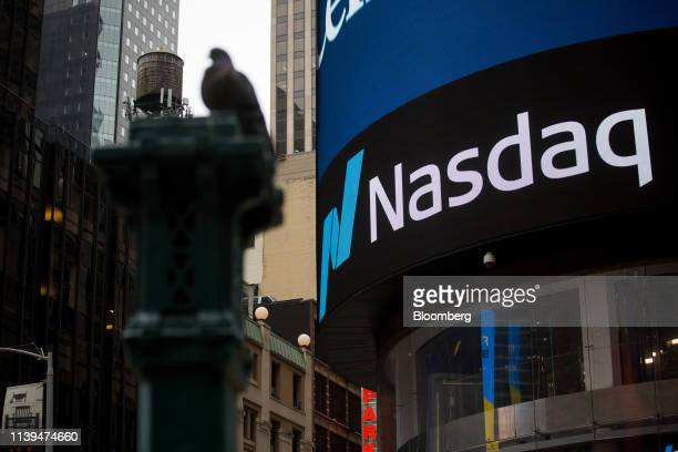 Monitor displays signage in front of the Nasdaq MarketSite in the Times Square area of New York, U.S., on Friday, April 26, 2019. U.S. Stocks edged...