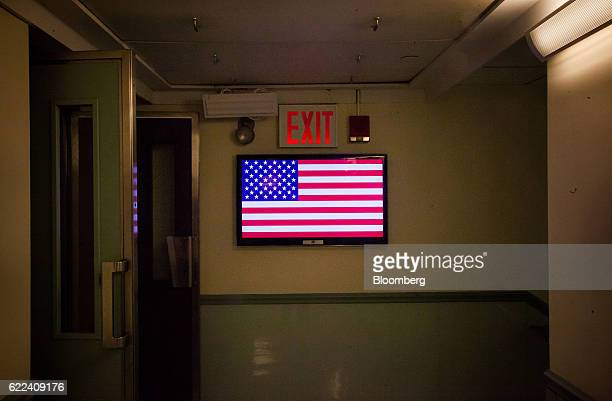 A monitor displays the American flag under an exit sign at the New York Stock Exchange in New York US on Friday Nov 11 2016 US stocks fluctuated in...
