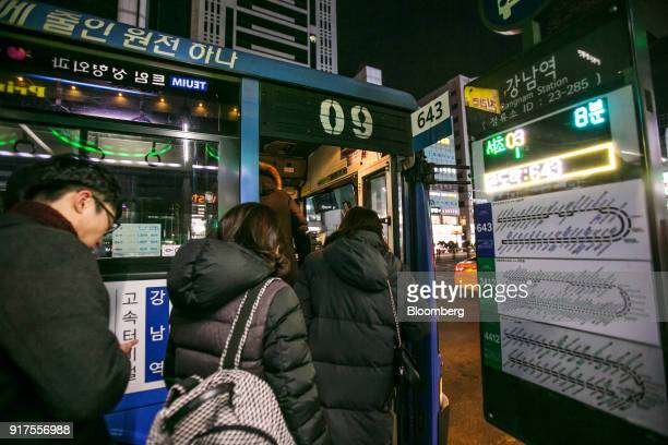 A monitor displays the estimated arrival times of buses as passengers board a bus at Gangnam Station in Seoul South Korea on Sunday Jan 28 2018 5G...