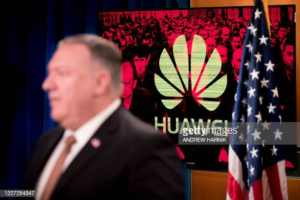 A monitor displays the logo for Huawei behind Secretary of State Mike Pompeo as he speaks during a news conference at the State Department in...
