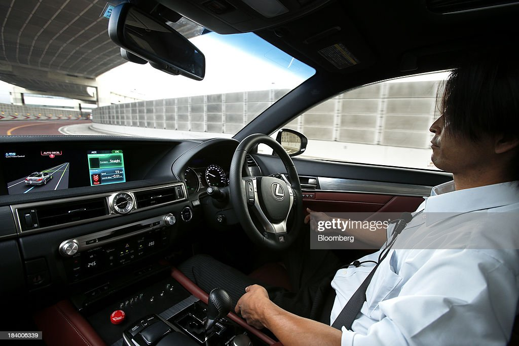 A monitor displays the status of the Lane Trace Control (LTC) technology as an employee drives a Toyota Motor Corp. Lexus vehicle, equipped with the Automated Highway Driving Assist (AHDA) support system, on an expressway during a media briefing on the company's advanced technologies in Tokyo, Japan, on Thursday, Oct. 10, 2013. Toyota, the worlds largest automaker, will introduce systems in about two years enabling cars to communicate with each other to avoid collision. Photographer: Kiyoshi Ota/Bloomberg via Getty Images