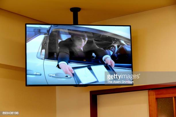 A monitor in the funeral hall displays an attendee in the driving seat hand envelope containing funeral offering at a firstever 'DriveThrough'...