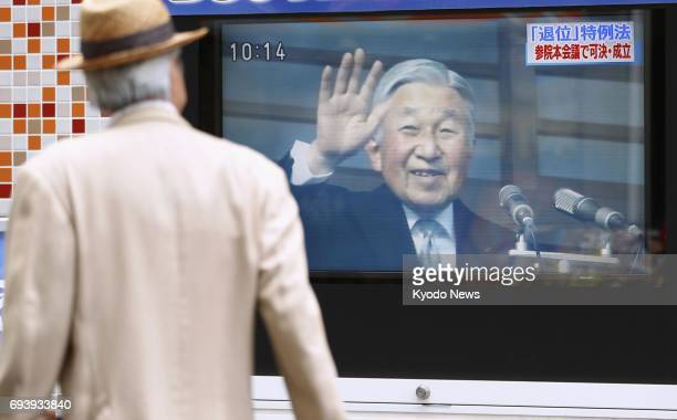 A monitor on a street in Tokyo announces the enactment of a law on June 9 to allow 83yearold Emperor Akihito to pass the throne to his elder son...