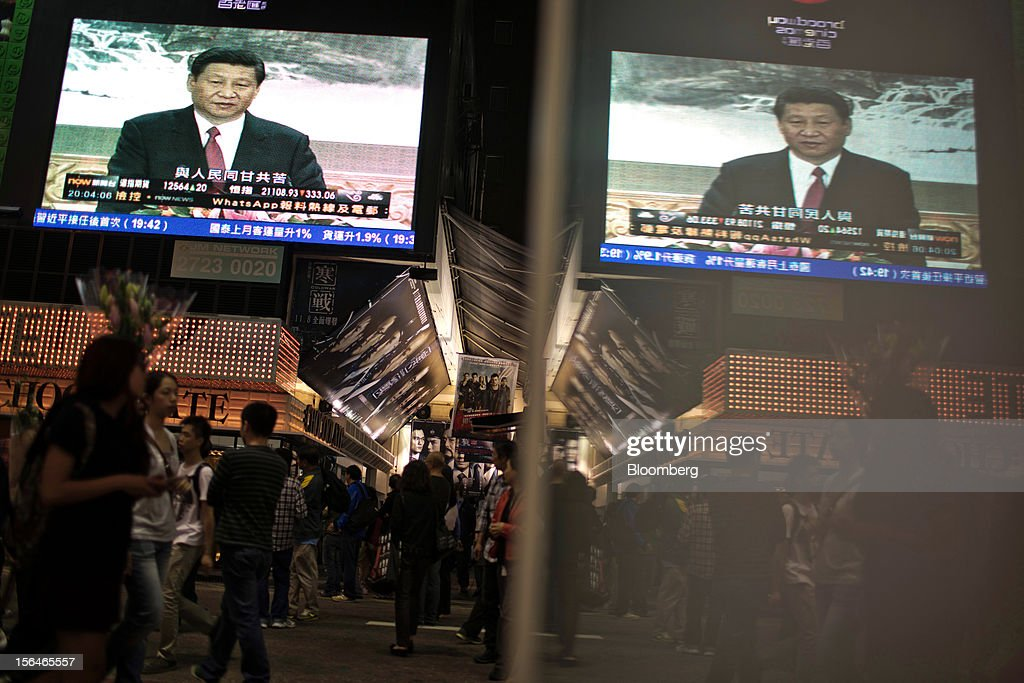 A monitor showing a news broadcast of Xi Jinping, general secretary of the Communist Party of China, during a news conference introducing the new Politburo Standing Committee, is reflected in a panel in the shopping district of Mong Kok in Hong Kong, China, on Thursday, Nov. 15, 2012. Xi Jinping replaced Hu Jintao as head of the Chinese Communist Party and the nation's military, ushering in the fifth generation of leaders who are set to run the world's second-biggest economy over the next decade. Photographer: Lam Yik Fei/Bloomberg via Getty Images