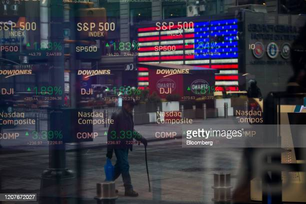 Monitors displaying stock market information are seen through the window of the Nasdaq MarketSite in the Times Square neighborhood of New York, U.S.,...