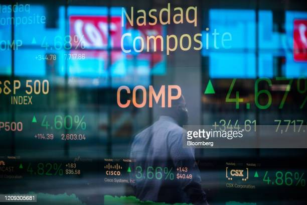 Monitors displaying stock market information are seen through the window of the Nasdaq MarketSite in the Times Square neighborhood of New York US on...
