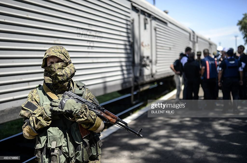 Monitors from the Organization for Security and Cooperation in Europe (OSCE) and members of a forensic team inspect a refrigerator wagon containing the remains of victims from the downed Malaysia Airlines Flight MH17, at a railway station in the eastern Ukrainian town of Torez on July 21, 2014. The head of a Dutch forensic team said on Monday a train, carrying the remains of victims from the Malaysian airliner crash, should set off later on Monday to a place where 'we can do our work'.