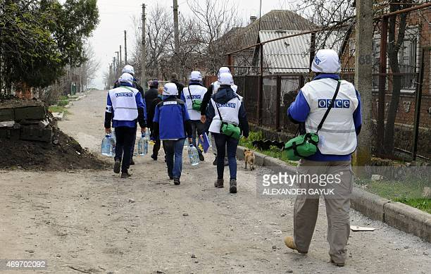 Monitors of the OSCE Special Monitoring Mission to Ukraine in Shirokine village walk along a path on April 14 2015 on the outskirts of the strategic...