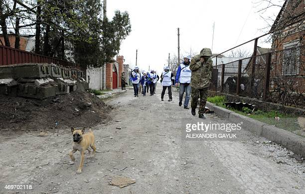 Monitors of the OSCE Special Monitoring Mission to Ukraine walk along a road in the village of Shirokine on April 14 2015 on the outskirts of the...