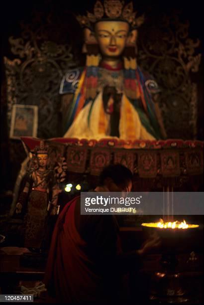 Monk adding yack butter to the temple lamps Pelkor Chode monastery Gyantse Tsang Tibet in China The Palcho Monastery or Pelkor Chode Monastery or...