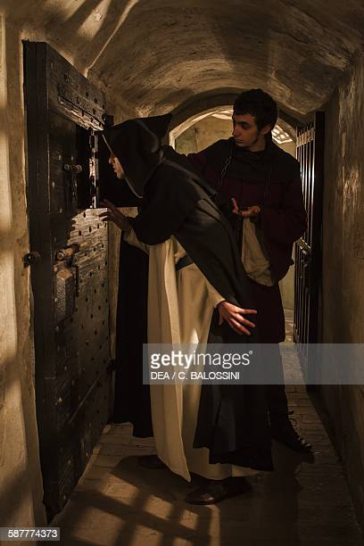 A monk and a jailer watching a woman accused of witchcraft in the dungeons of a castle Italy Northern 15th century Historical reenactment