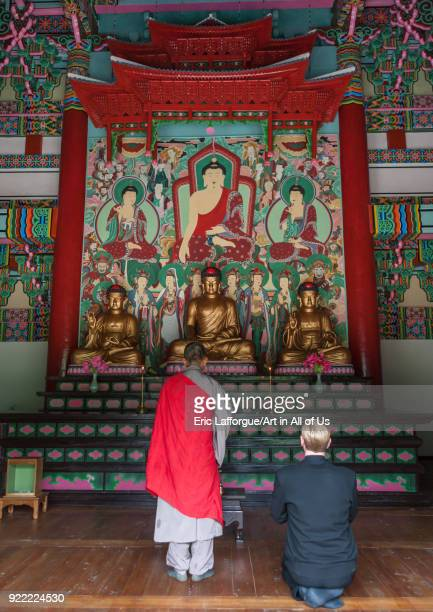 Monk and tourist praying in front of the altar of Kwangbok temple Pyongan Province Pyongyang North Korea on May 21 2009 in Pyongyang North Korea