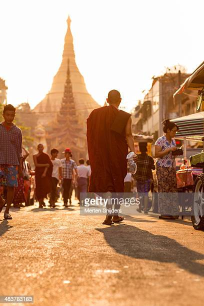 monk approaching shwedagon pagoda - merten snijders stock pictures, royalty-free photos & images