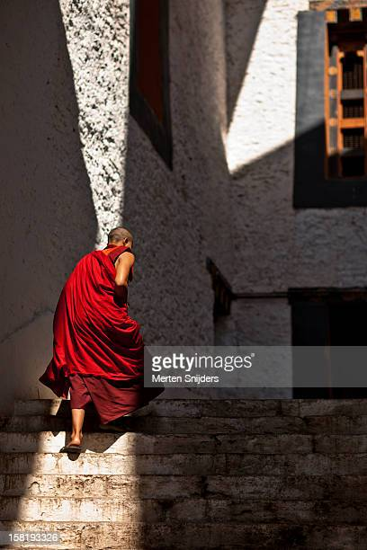 monk ascends stairs at punakha dzong - プナカ ストックフォトと画像
