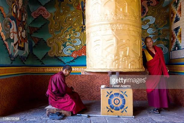 monk at prayer wheel, punakha dzong at the convergence of two rivers mo chhu and pho chhu, punakha, bhutan - プナカ ストックフォトと画像