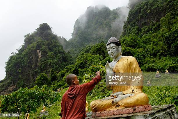 A monk cleans one of 500 Buddha statues erected at the foot of a hill near the Thayet U Min pagoda