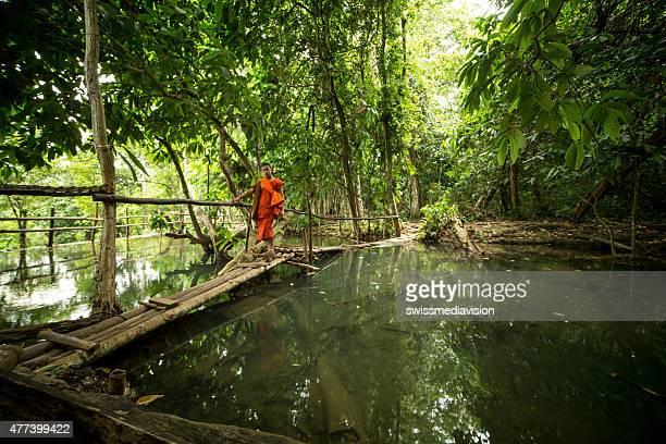 Monk crossing bamboo bridge at the Kuang Si waterfalls,Laos