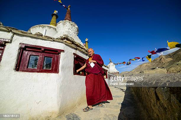 Monk dressed in red cloths is walking around Lamayuru Gompa the oldest and largest existing monastery in Ladakh turning prayer wheels for religious...