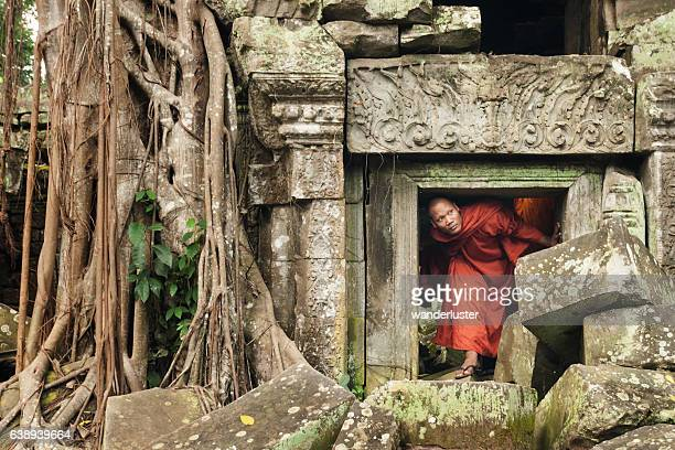 monk exploring old ruins - angkor stock photos and pictures