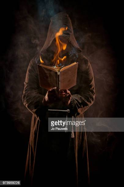 monk holding burning book - cape stock pictures, royalty-free photos & images