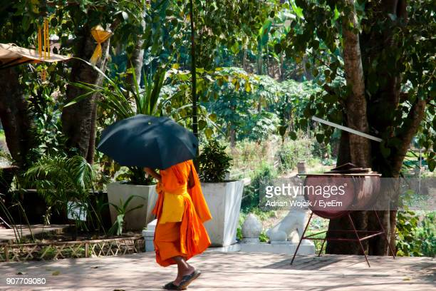 monk holding umbrella while walking on road - adrian monk photos et images de collection