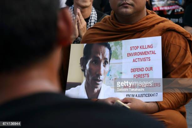 A monk holds a poster of slain prominent environmental activist Chut Wutty during a commemoration rally for the fifth anniversary of his death Chut...