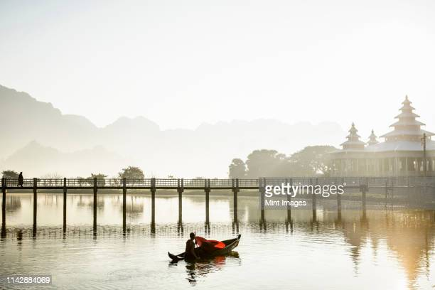 a monk in a shallow boat under a bridge in a mountain landscape - yangon stock pictures, royalty-free photos & images