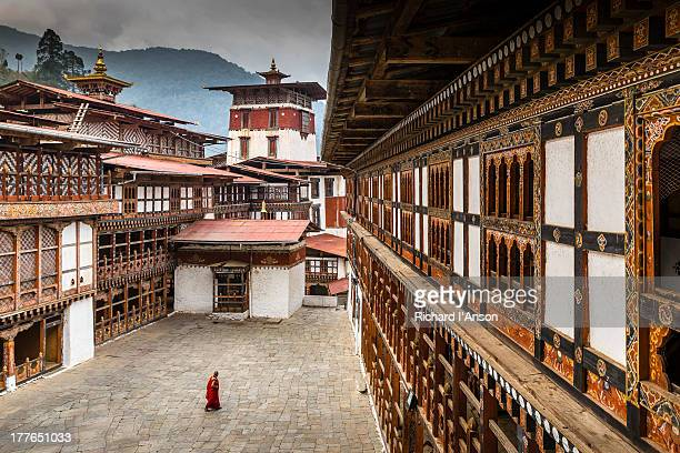 monk in courtyard at trongsa dzong - bhutan stock pictures, royalty-free photos & images