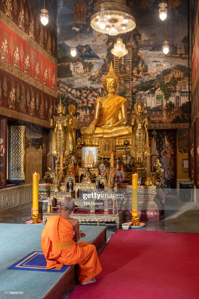 Monk in front of Buddha images. : Stock Photo