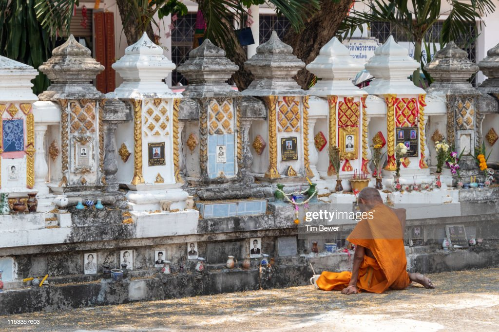 Monk in front of crypt for people's ashes. : Stock Photo