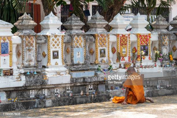 monk in front of crypt for people's ashes. - tim bewer stockfoto's en -beelden