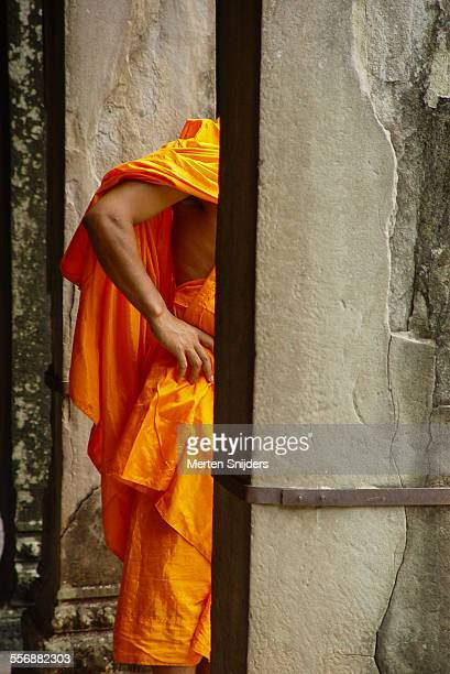 monk in orange robe behind temple pilar - angkor stock photos and pictures