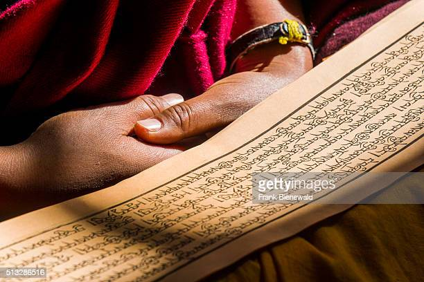 A monk is reading a prayer book inside the monastery Thupten Chholing Gompa detail of the prayer book and his hands