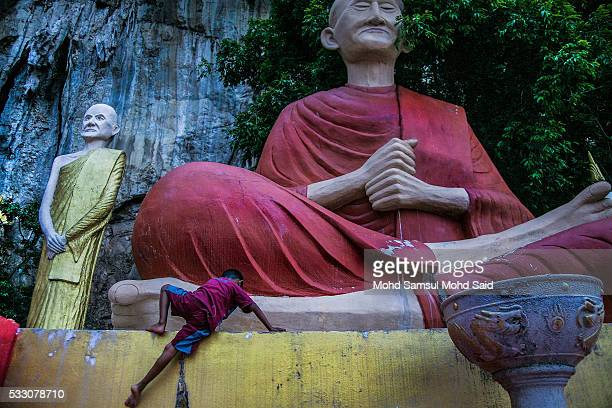A monk is seen clean the Buddha statue inside the temple on the eve of Vesak celebrations outside Kuala Lumpur on May 20 2016 in Ipoh Malaysia...