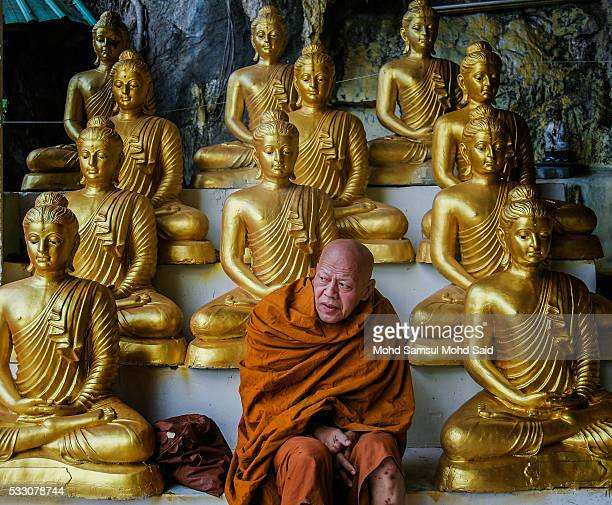 A monk is seen sit near the Buddha statue on the eve of Vesak celebrations outside Kuala Lumpur on May 20 2016 in Ipoh Malaysia Buddhists across the...