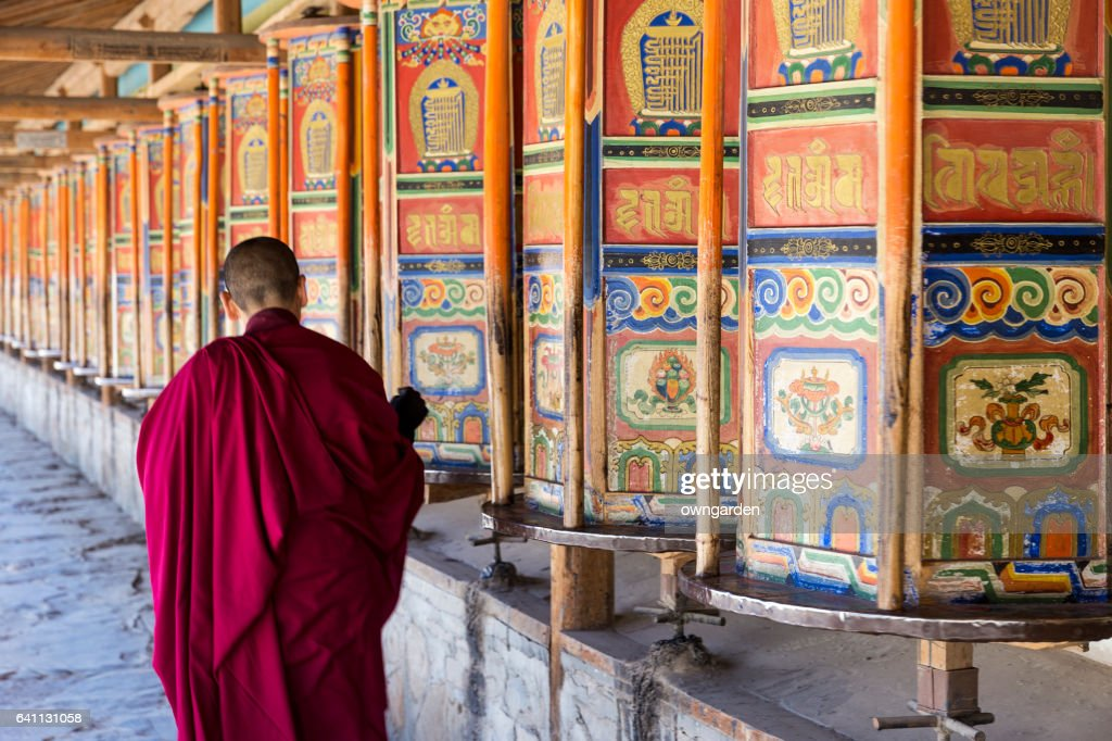 A monk is walking and turning huge and colorful prayer wheels in Labrang Monastery : Stock Photo