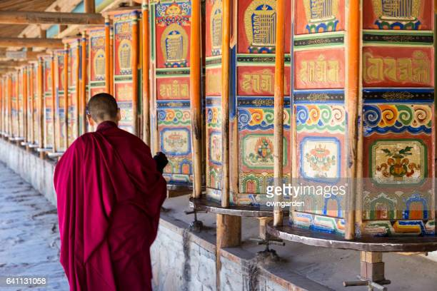 A monk is walking and turning huge and colorful prayer wheels in Labrang Monastery