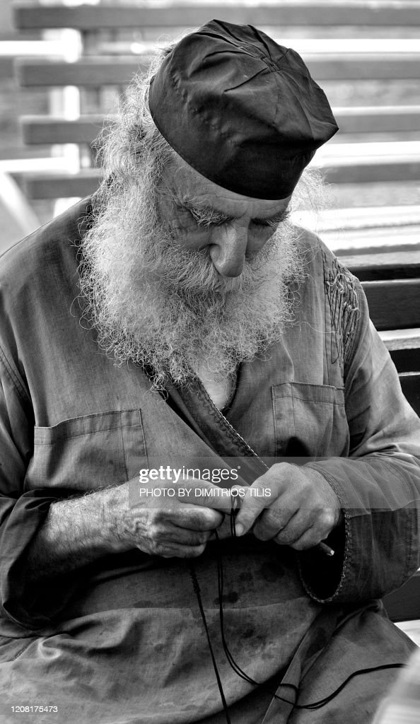 Monk knitting a prayer : Stock Photo