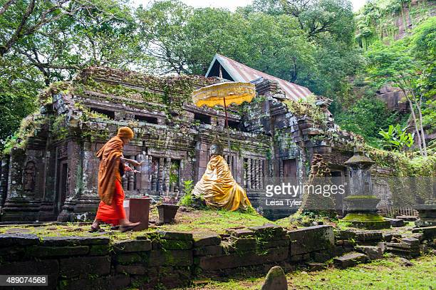 WAT PHU CHAMPASAK CHAMPASSAK LAOS A monk laying offerings at Wat Phu a ruined Khmer Hindu temple complex dating back to the 5th century and believed...