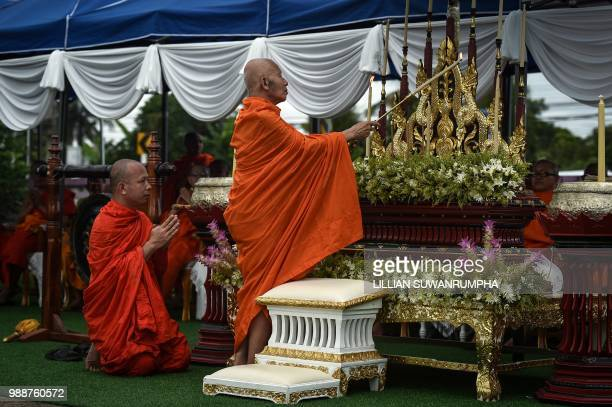 A monk lights a candle at an altar during a Buddhist prayer for the missing children near Tham Luang cave at the Khun Nam Nang Non Forest Park in the...