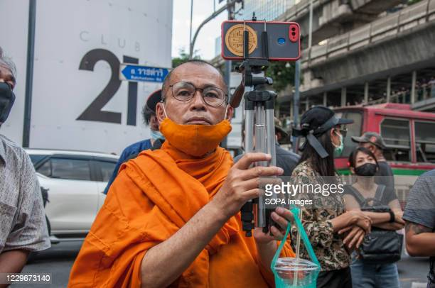 Monk live streaming with his mobile phone during the demonstration. Pro-democracy protesters gathered at Ratchaprasong intersection and marched...