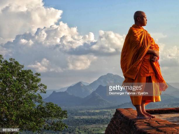 Monk Looking Away While Standing On Retaining Wall Against Sky