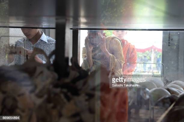 A monk looks at human skulls displayed in a memorial tower at the Choeung Ek killing fields during a memorial service to mark the 42nd anniversary of...