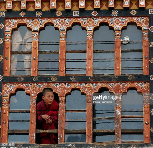 A monk looks out of the classroom window at the Dechen Phodrang monastery April 2 2008 in Thimphu Bhutan About 475 monks reside at the governmentrun...