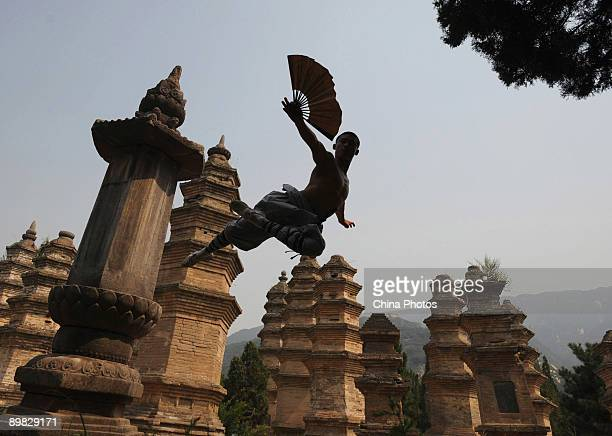 A monk practices kung fu at the Shaolin Temple on the Songshan Mountain on August 15 2009 in Dengfeng of Henan Province China Shaolin Temple built in...
