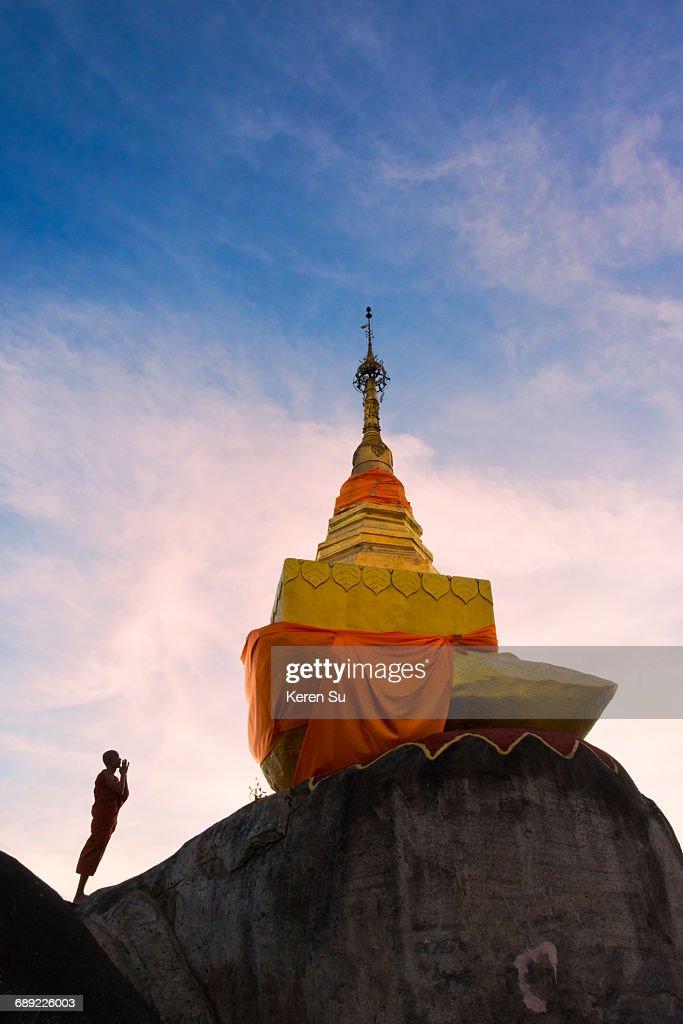 Monk praying at a golden pagoda on Mt Kyaiktiyo : Stock Photo