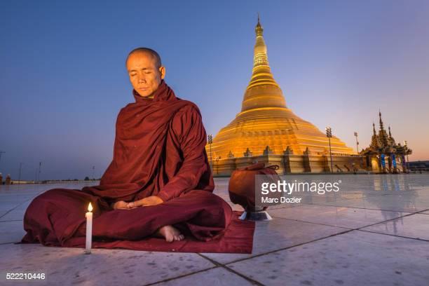 monk praying in ouparta thandi zedi pagoda - naypyidaw stock pictures, royalty-free photos & images