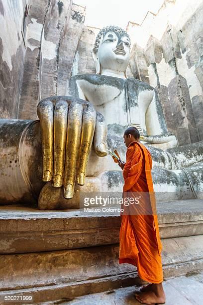 Monk praying near Giant Buddha hand, Thailand