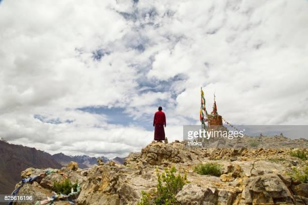 Monk praying on hill